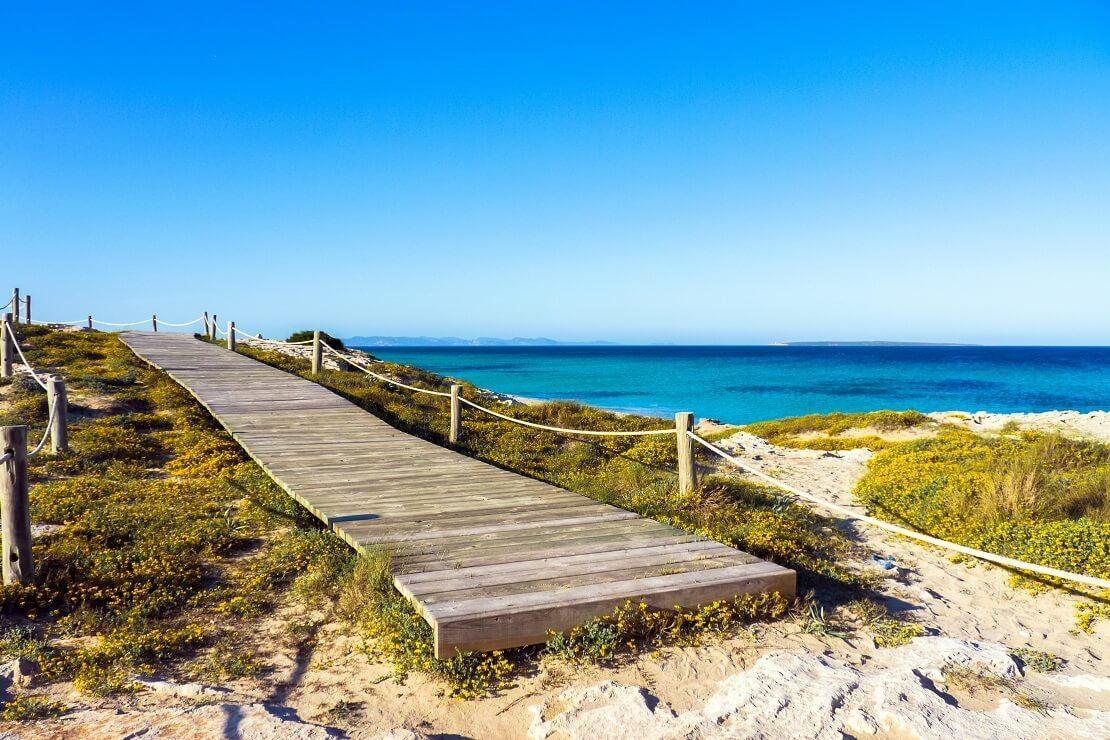 Pier am Strand am türkis blauen Wasser unter klarem Himmel