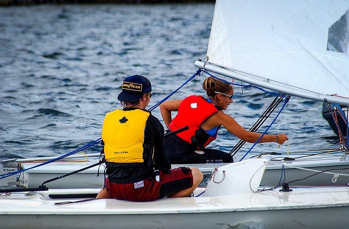 Zwei Segler auf einem Boot mit Rettungswesten
