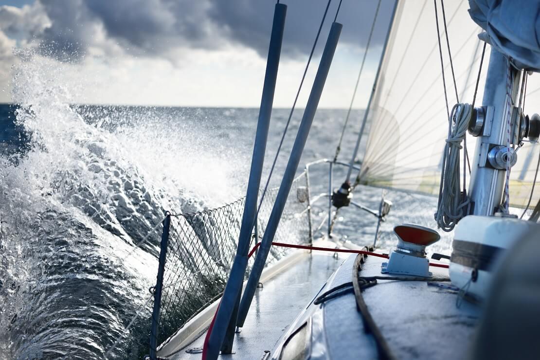 Ein Segelboot fährt auf dem Wasser an einer Welle