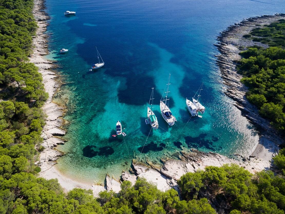 türkis blaues Meer in welchem Botte segeln umgeben von grünen Bäumen