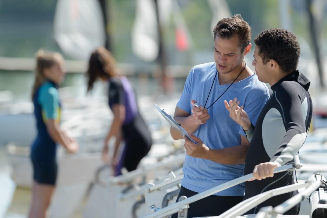 Segler spricht mit einem Segellehrer am Bootssteg