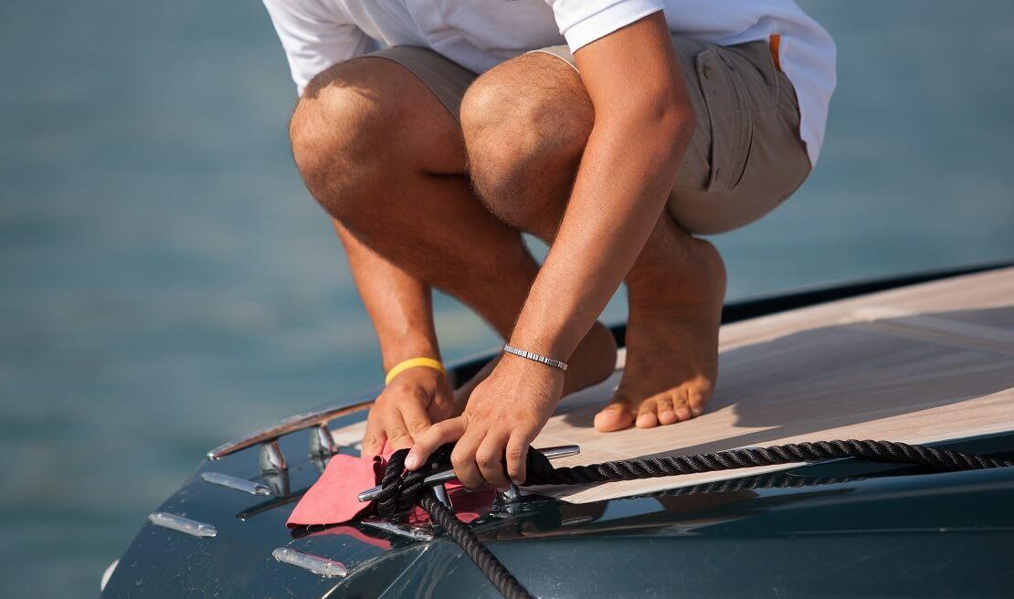 Segler reinigt die Oberfläche seines Bootes mit einem Lappen