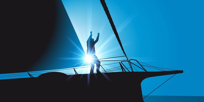 Segler steht auf einem Boot vor der Sonne und jubelt