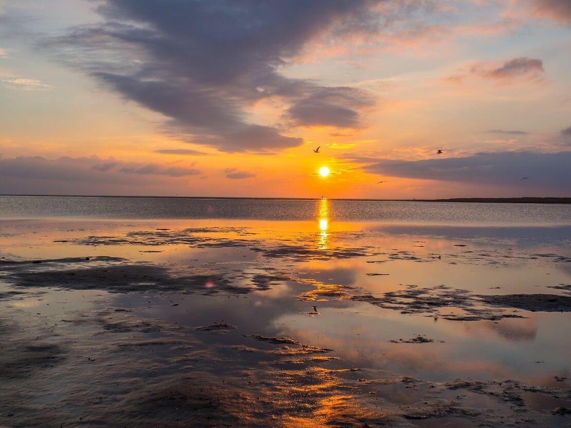 Der Sonnenuntergang vor Wolken und dem Meer