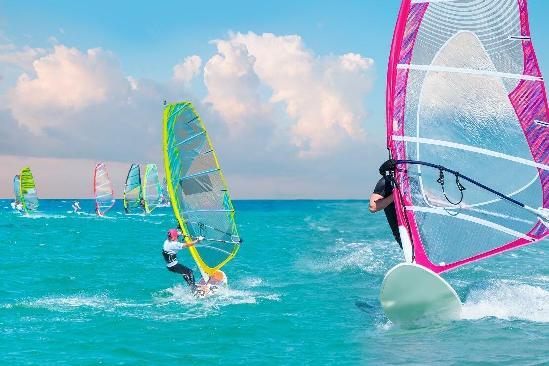 Einige Personen stehen auf einem Windsurfboard auf dem Wasser