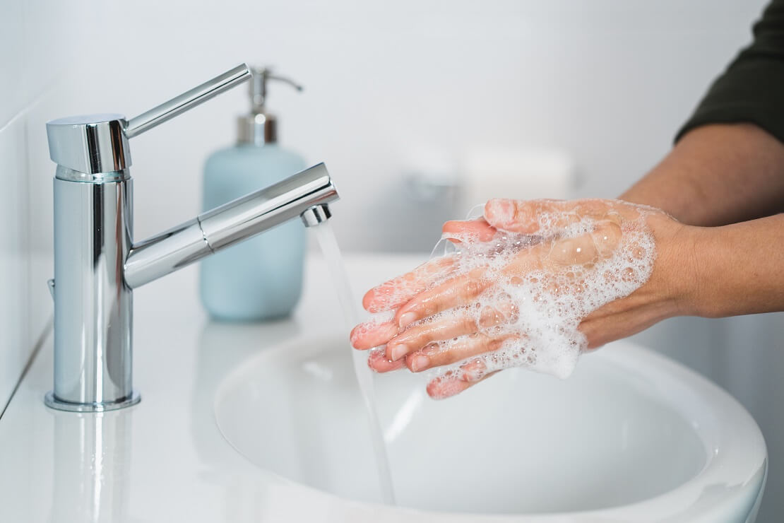Person wäscht sich an einem Waschbecken die Hände mit Seife