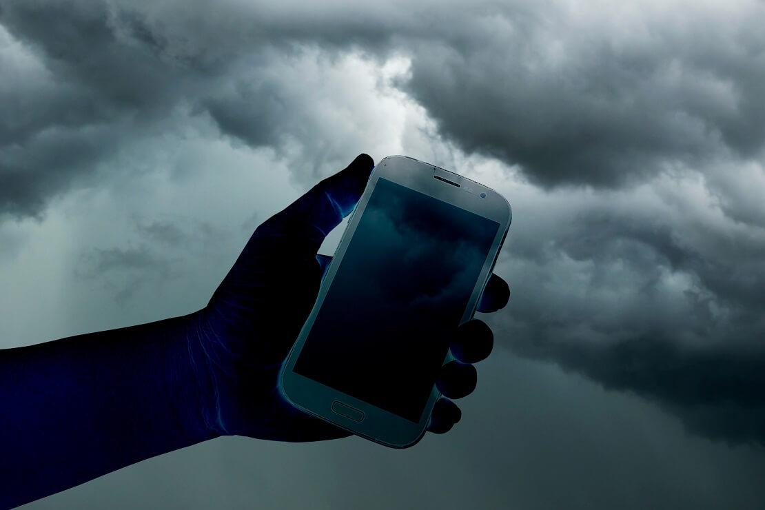 Ein Handy wird hochgehalten im Hintergrund sind dunkle Wolken zu sehen
