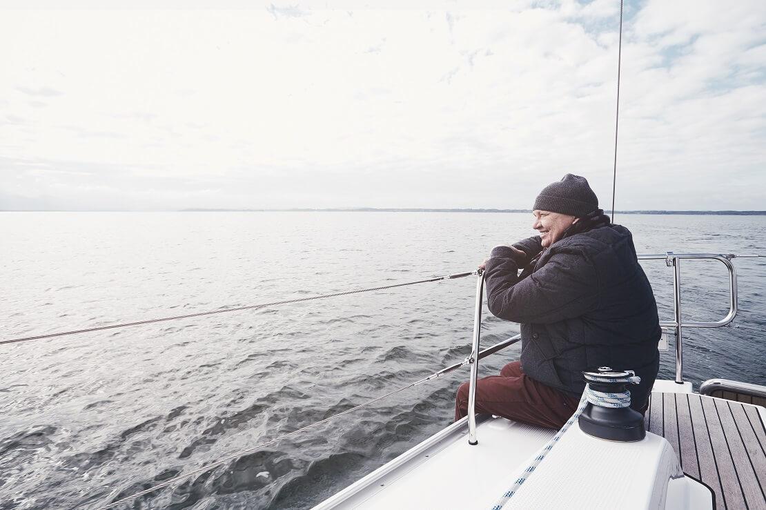 Mann sitzt auf einem Boot und schaut auf das Meer