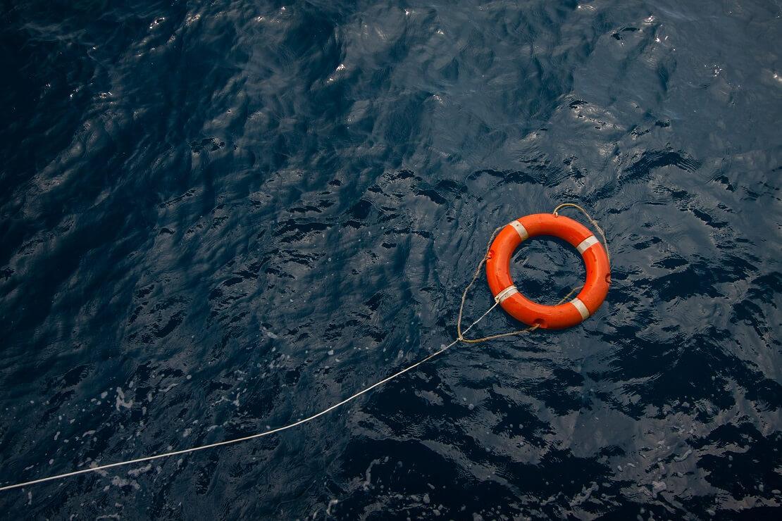 Ein Rettungsring schwimmt im Wasser an einem Seil befestigt