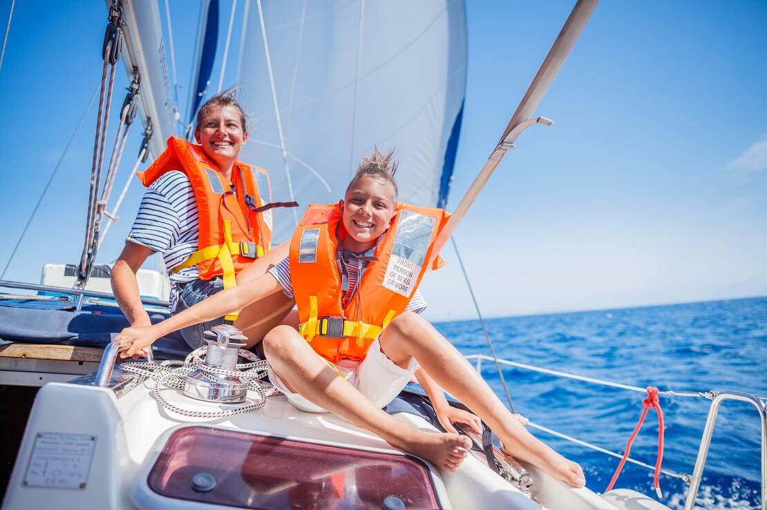 Kinder sitzen mit einer Schutzweste auf einem Segelboot