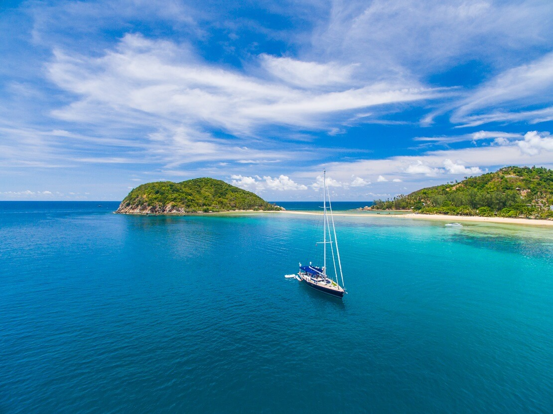 Boot segelt auf türkisem Wasser vor einer Küste