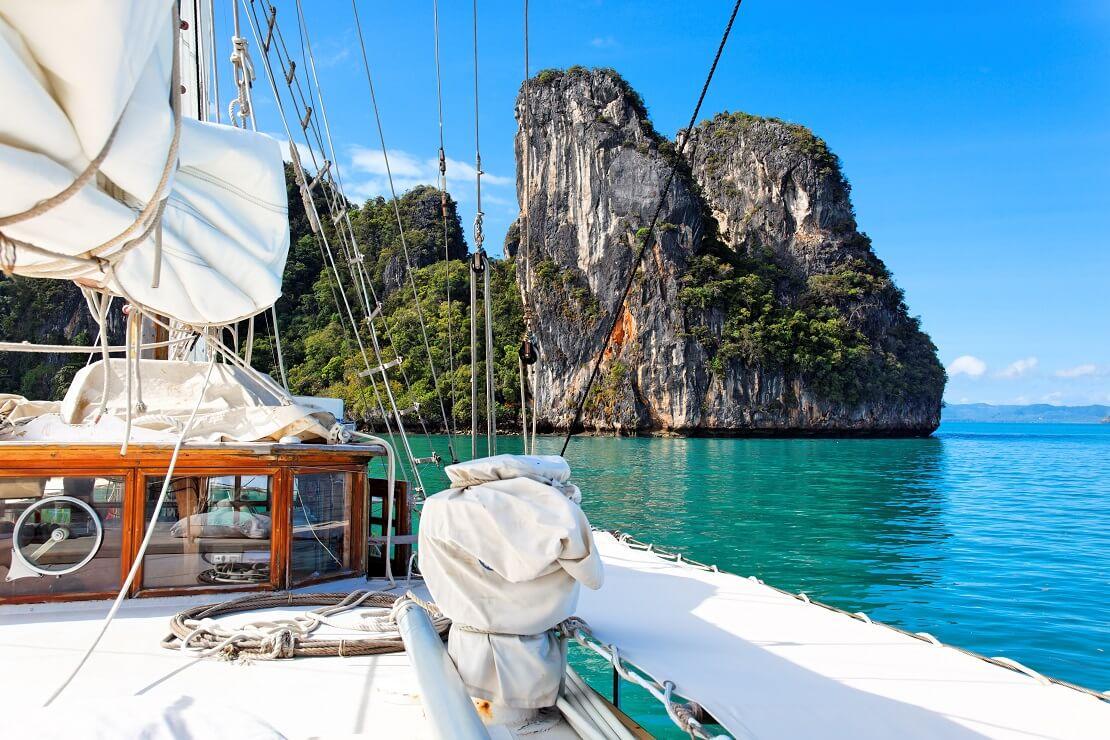 Boot segelt auf türkisem Meer im Hintergrund sind große Felsen