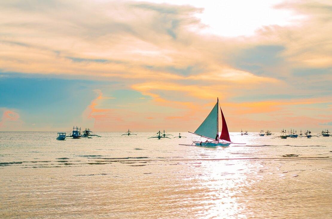 Boote segeln auf dem Meer bei Sonnenuntergang