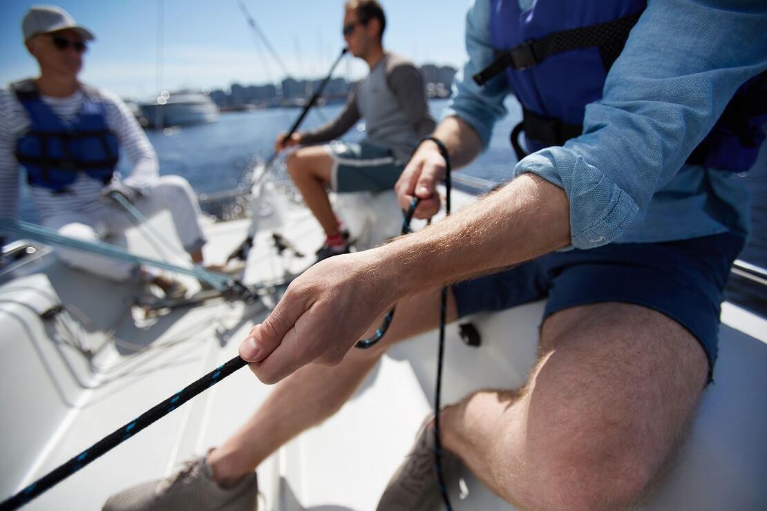 Segler hält eine Leine auf einem Boot stramm im Hintergrund sitzen zwei Personen