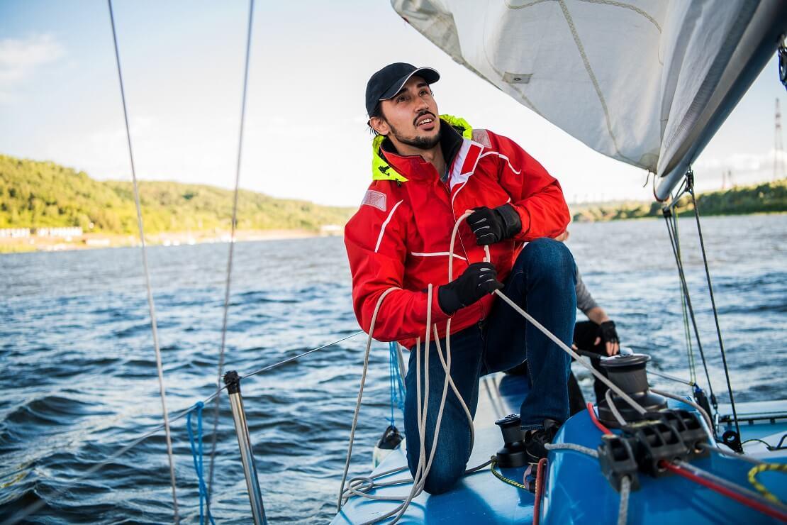 Mann auf einem Boot im Wasser zieht an einem Seil