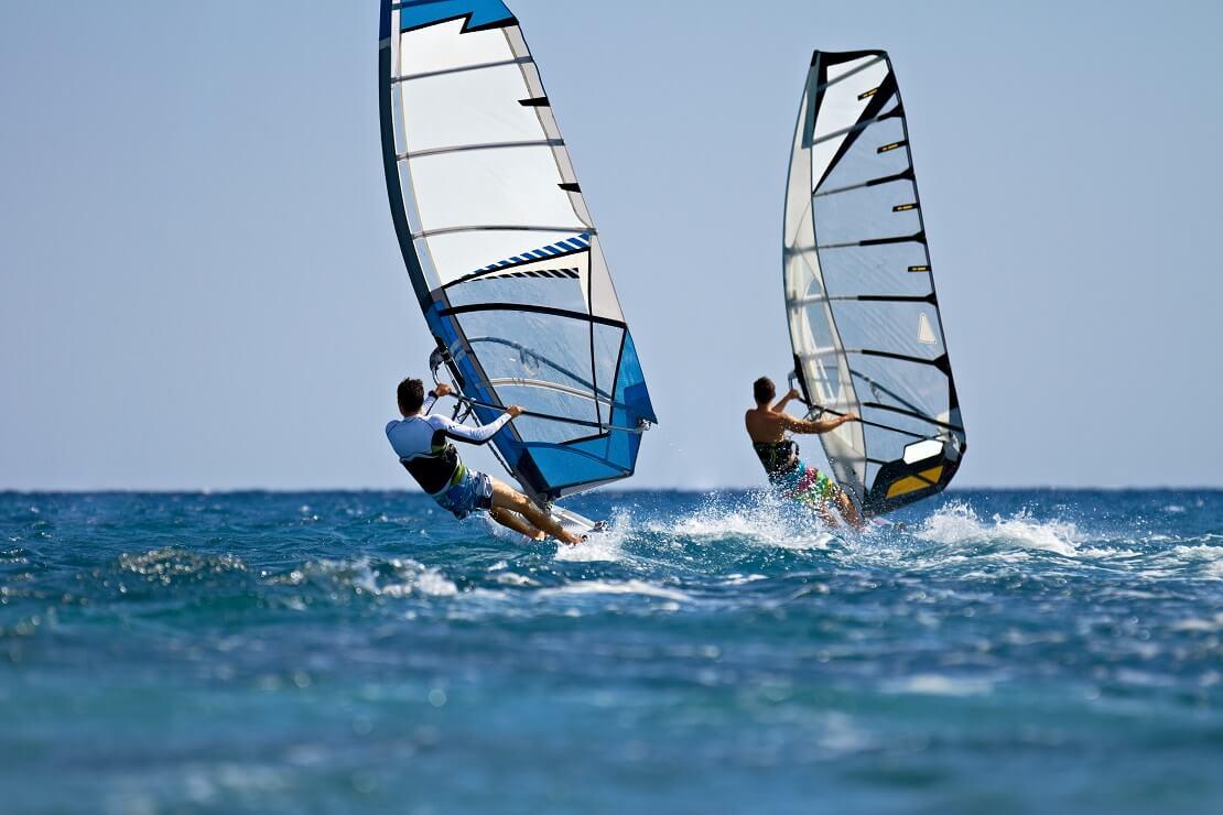 Zwei Windsurfer auf dem blauen Meer