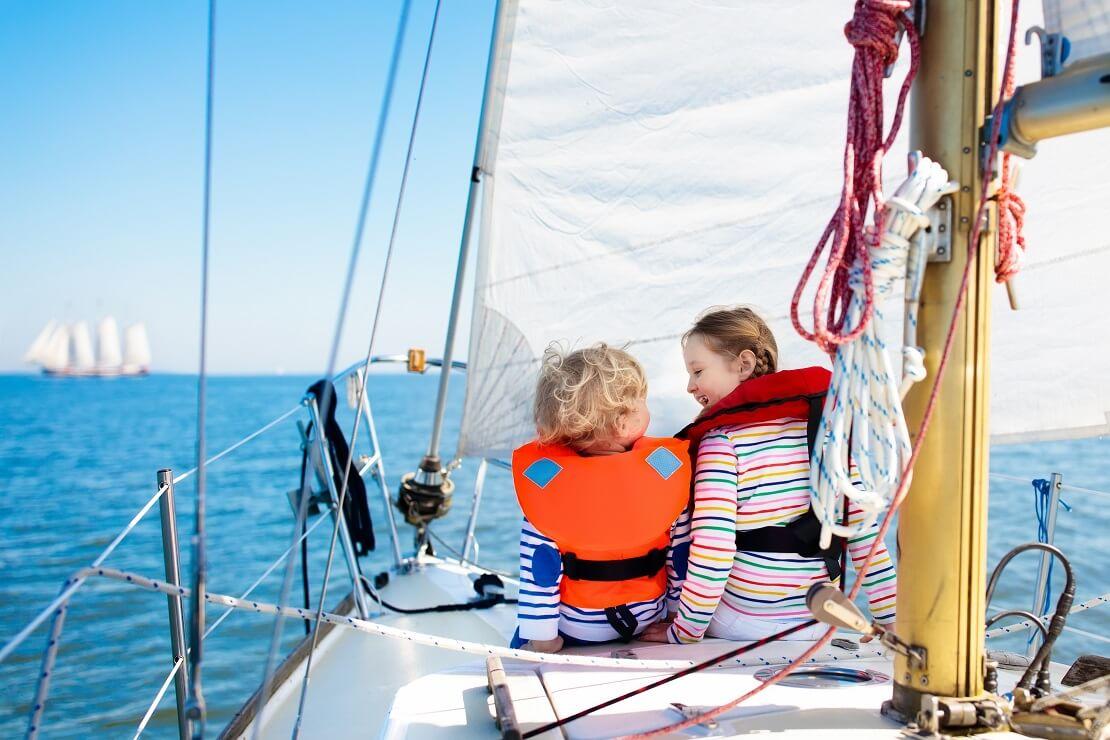 Kinder sitzen mit Rettungsweste auf einem Segelboot
