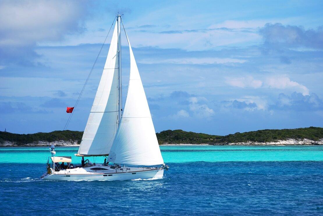 Segelboot schwimmt vor einer Insel bei den Bahamas