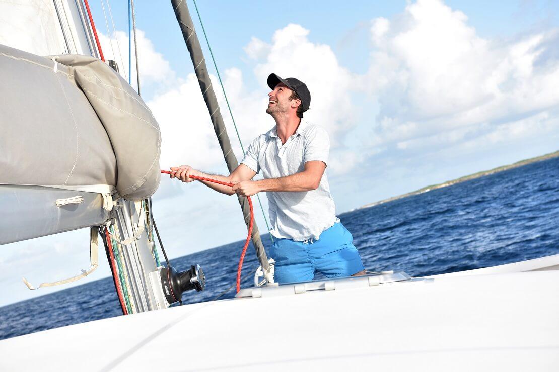 Skipper zieht mit einem Tau am Segel