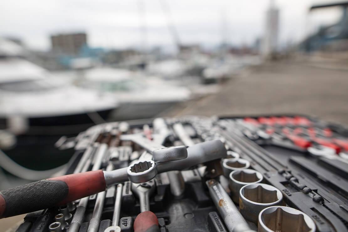 Werkzeuge an einem Hafen vor Segelbooten