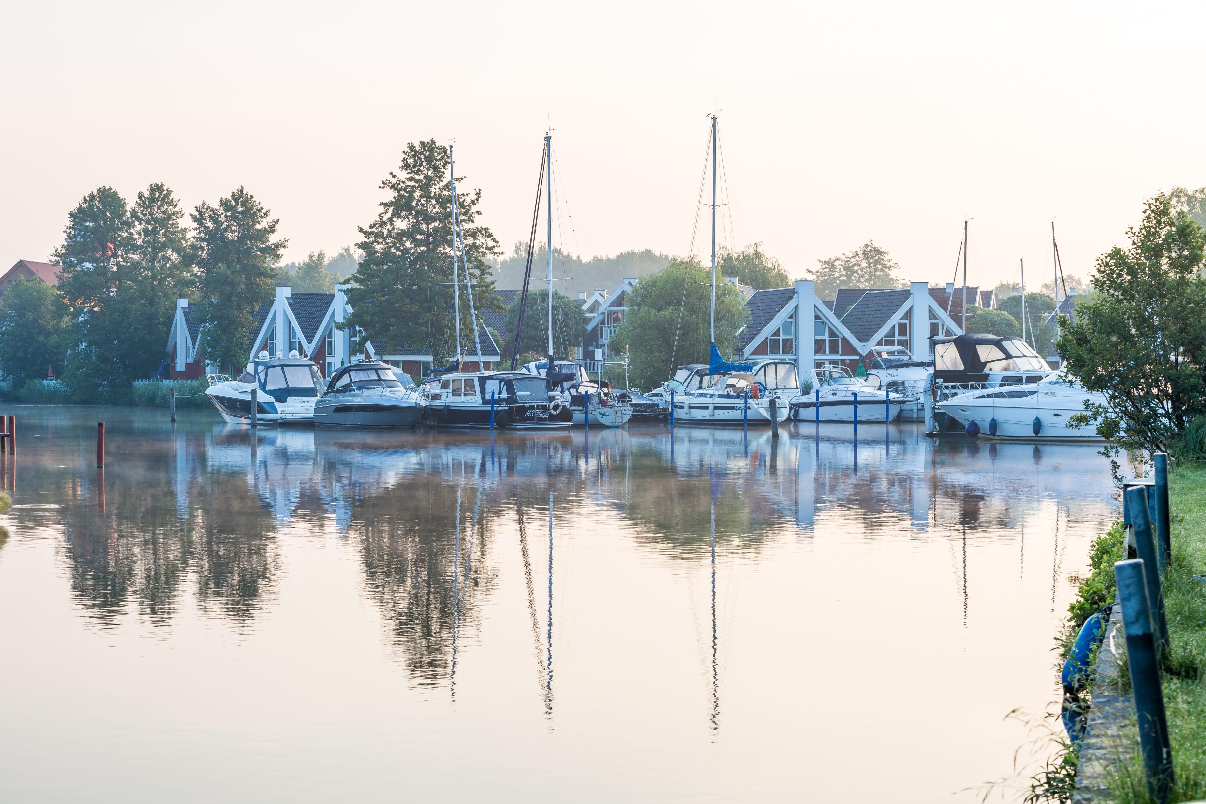 Segelboote ankern an einem Steg im Hintergrund stehen Ferienhäuser