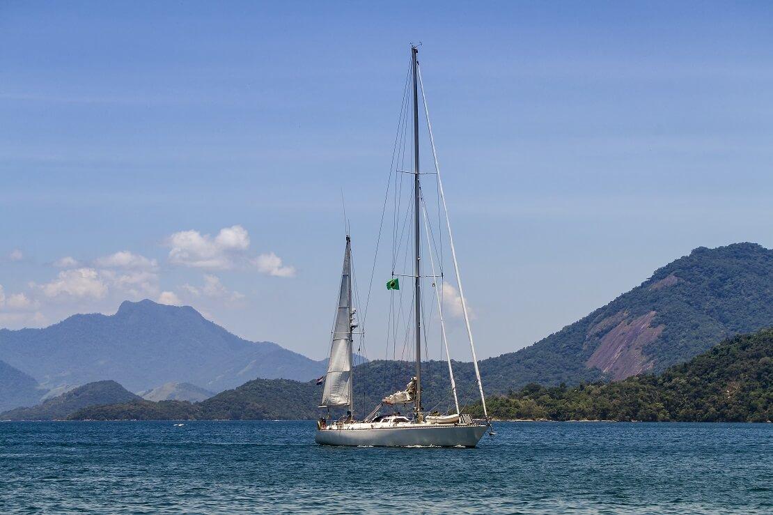 Segelboot auf dem Wasser im Hintergrund Berge