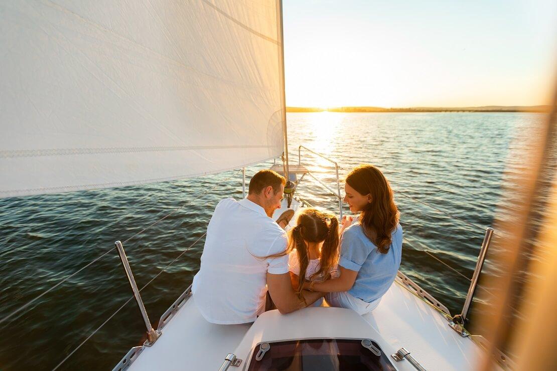 Mann und Frau mit einem Kind an Deck von einem Segelboot bei Sonnenuntergang