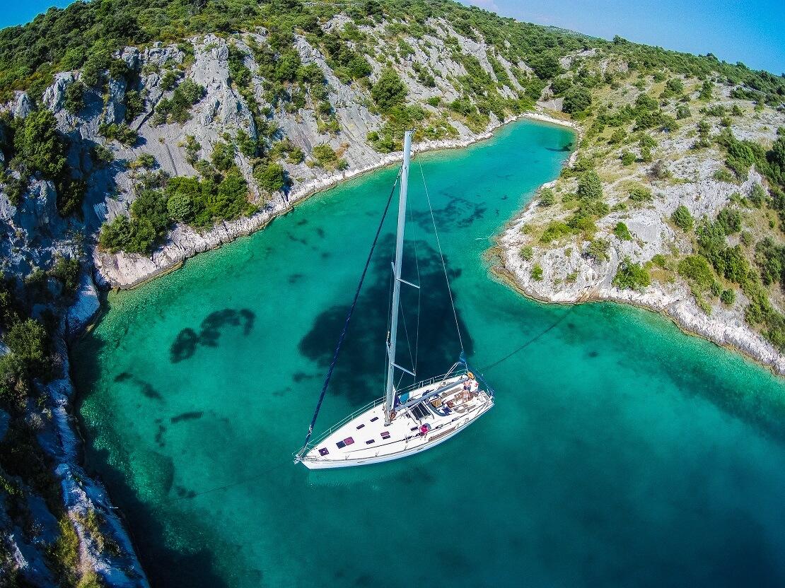 Segelboot in einer Bucht im türkisblauen Wasser in Kroatien