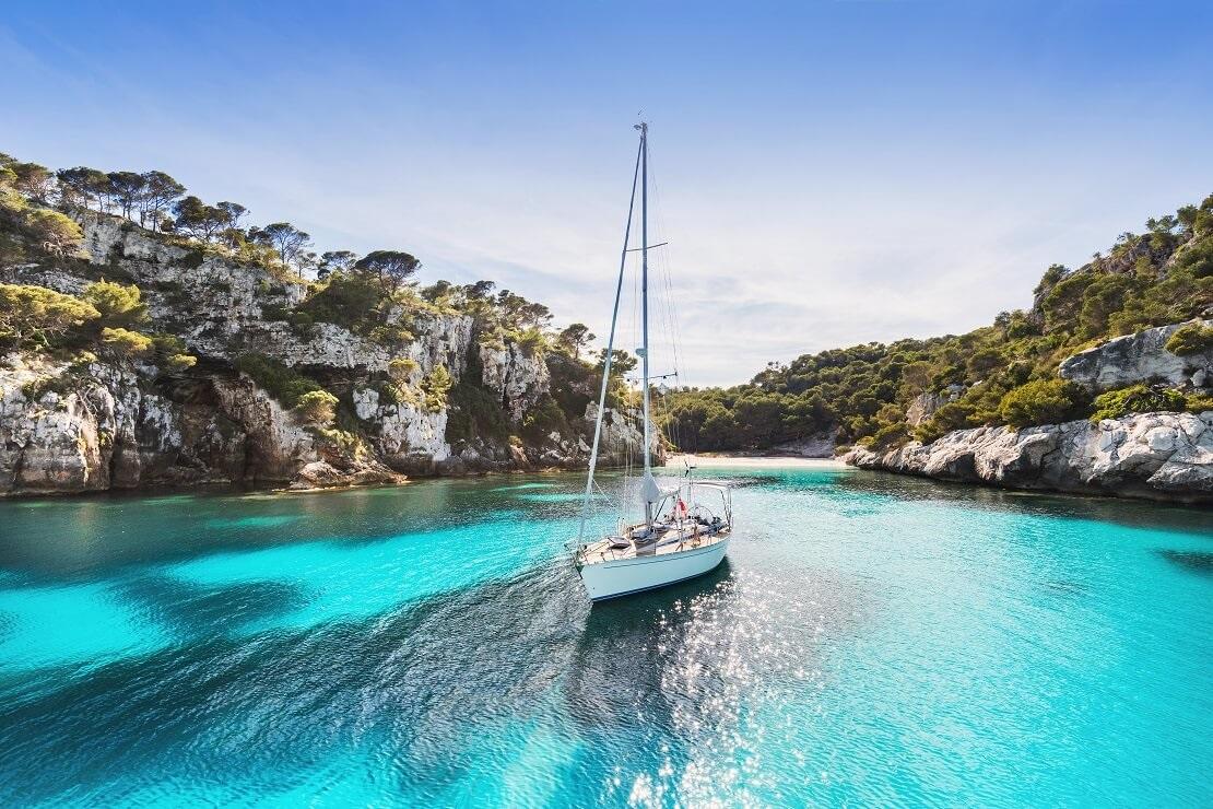 Boot segelt auf türkisblauem Wasser vor einer felsigen Küste