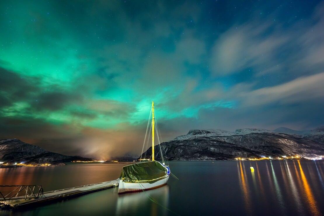 Die Polarlichter Norwegens mit einem Segelbott im Vordergrund