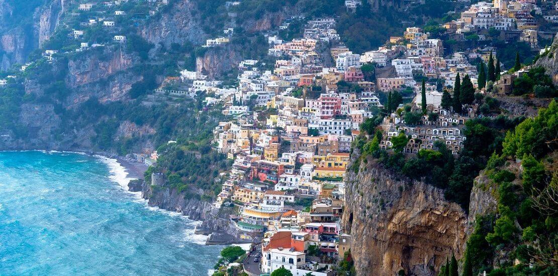 Segeln an der Amalfiküste vor pastellfarbenen Häusern im Felsen